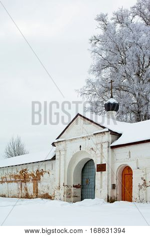 White winter trees and doorway in big wall in Uglich