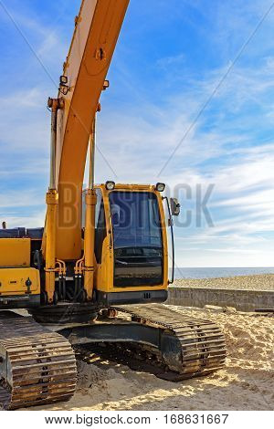 Excavator cabin on the beach with blue sky and sea in the background