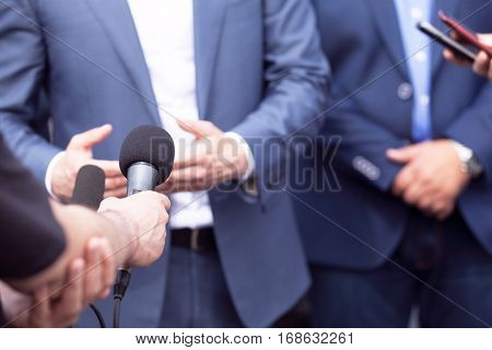 Reporters making interview with businessman, politician or spokesman. News conference.