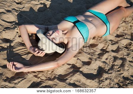 girl in bathing suit sunning on a sandy beach