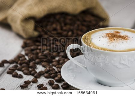 Cup of Cappuccino with Coffee Beans / Composition of Cup of Cappuccino and sack of coffee beans on white wooden table