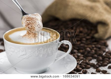 Cup of Cappuccino with Spoon and foam / Composition of Cup of Cappuccino and spoon with foam, sack of coffee beans on white wooden table