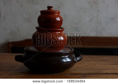 Clay pots for cooking on brown wooden table
