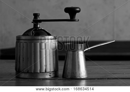 Vintage rustic, coffee, sugar and pepper mill and turka on wooden table in old black and white style