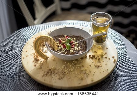 Chocolatiers breakfast with oatmeal, puffed rice, cereals and dried strawberries and green tea prepared in a white bowl. Gold horseshoe for good luck.