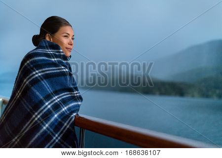 Cruise ship passenger on Alaska travel vacation enjoying scenery at dusk on suite balcony deck with wool throw in cold weather. Asian tourist woman relaxing on summer holiday cruising adventure.
