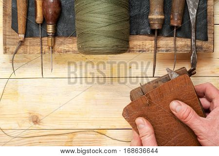 Leather craft tools on a wooden background. Craftmans working with leather using crafting DIY tools. Piece of hide and working handmade tools on a work table. Top view. Copy space.