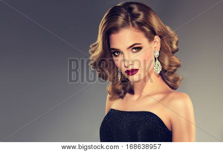 Beautiful model girl with curly hair .Young woman with short wavy hairstyle with long shine jewelry earrings .