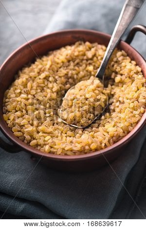 Bulgur in a copper bowl and metal spoon on the napkin vertical