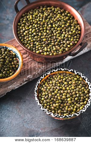 Green mung beans in bowls on wooden stand partial blur vertical