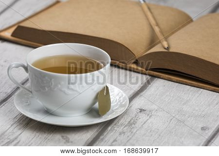 Cup of Tea and notebook/ Composition of white cup of tea and vintage notebook with pencil on white wooden table