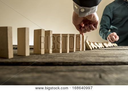 Businessman stopping the domino effect of falling wooden blocks initiated by a colleague or business competition in a concept of success and solving problems.