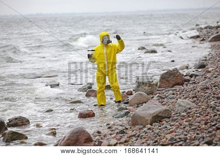 Specialist in protective suit checking sample of water in container on rocky sea, ocean shore