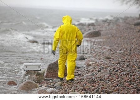 scientist in protective suit with silver case walking on rocky beach - back view