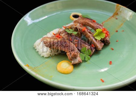 Grilled pork ribs and rice on plate black background