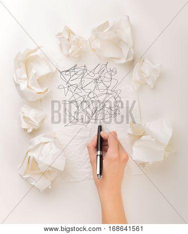 Female hand next to a few crumpled paper balls drawing random scribbles