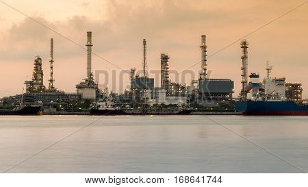 Refinery over river with cloudy sky background