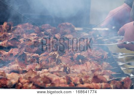Barbeque sticks with meat on the grill and heavy smoke above brazier.