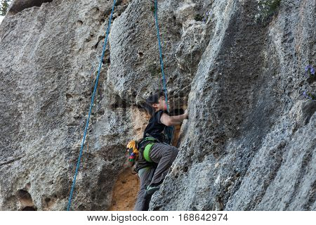 Boy climbing on a limestone wall, rock on the background