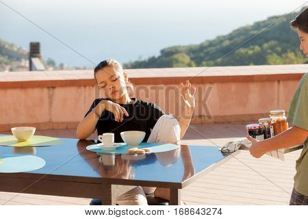 Boy brings breakfast to his sister, outdoors