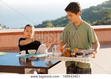 Satiates girl refuses breakfast, boy with a tray with many jams in the foreground