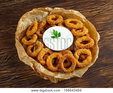 Fried Breaded Onion Rings with sauce on baked pepper.