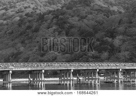 Black and White Togetsukyo bridge pass through Arashiyama forest during Autumn season Japan