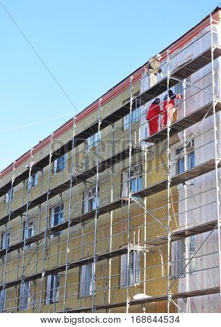 KIEV UKRAINE - January 26 2017: Builders repair facade thermal insulation. Energy efficiency house wall renovation for energy saving. Exterior house wall heat insulation with insulator and mineral wool