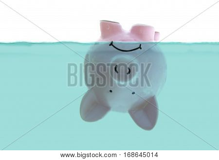 frowning pink piggy bank floating upside down under water on white