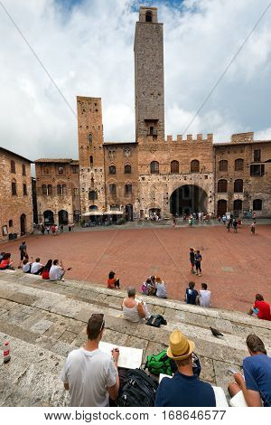 SAN GIMIGNANO ITALY - JULY 12 2014: Tourists visit the ancient and medieval Piazza del Duomo (Cathedral square). San Gimignano (UNESCO heritage) Siena Tuscany Italy