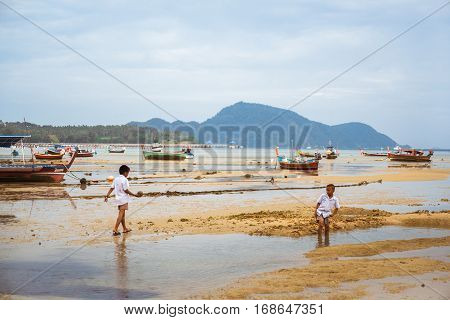 THAILAND PHUKET ASIA - FEBRUARY 1 2017: Thai children schoolchildren playing on the beach in the bay with the old Fishing boats at low tide.