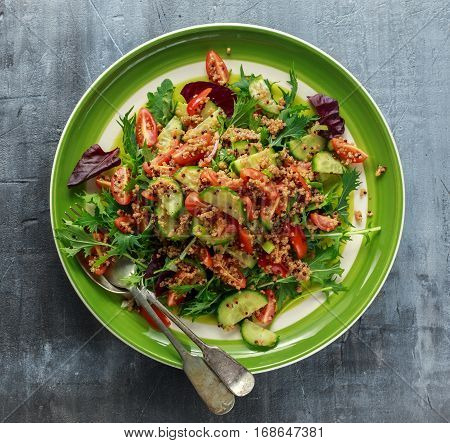 Quinoa tabbouleh salad with tomatoes, cucumber green onion. Concept healthy food.