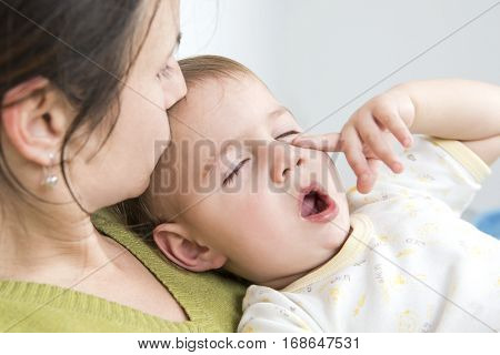 Mother kissing her sleepy ill baby