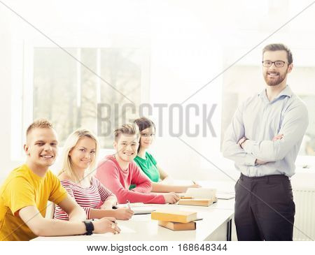 Group of teenage students and a teacher at the lesson in the classroom. Education, school, college and university concept. Hipster color.