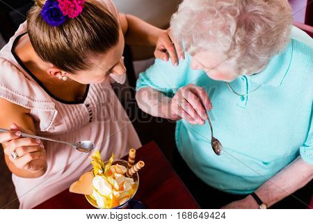 Senior woman and granddaughter having fun eating ice cream sundae in cafe