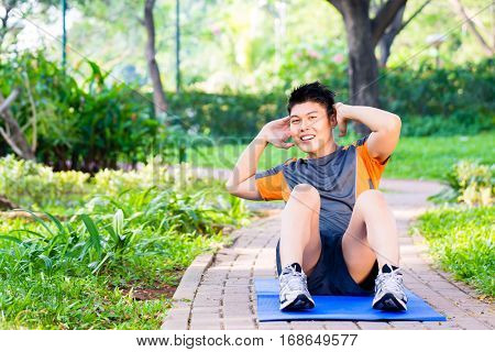 Asian man doing crunches for six pack training in park