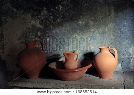 Still live with ancient pottery items in a stone counter and lit by a window