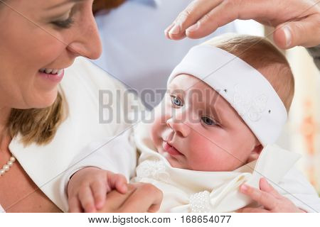 Mother with her baby at the christening ceremony, with the priest holding his hand above the babys head