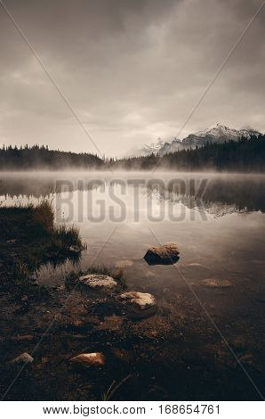 Lake Herbert in a foggy morning with glaciers mountain and reflection in Banff National Park, Canada