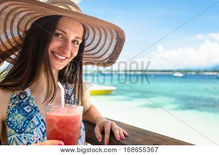 Woman in beachwear enjoying drink in beach cafe at sea