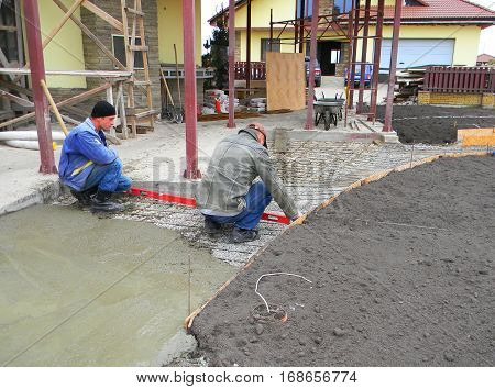 KIEV - UKRAINE January - 20 2017: Two contractors building new concrete pavement for garden pathway and house terrace.