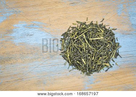 iccha kariban loose leaf  green tea, a heap over grunge wood with a copy space, top view