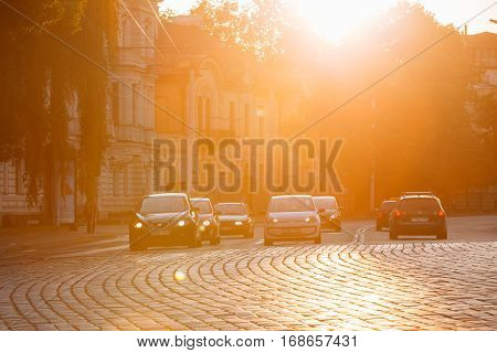 Vilnius, Lithuania - July 8, 2016: Traffic On Zygimantu Street In Old Town. Moving Cars With Luminous Headlights On The Paved Road In Yellow Sunlight Of Sunset Sunrise.