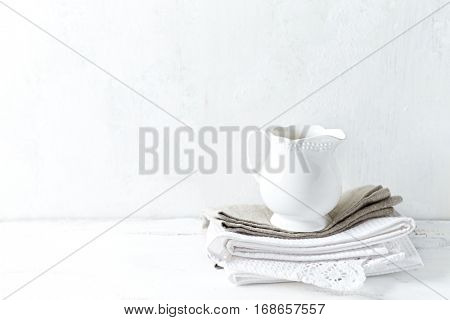 White ceramic milk jug on tea towels