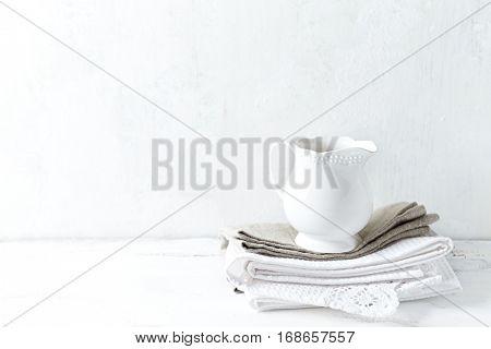 White ceramic milk jug on tea towels