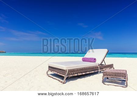 Deckchair on sandy tropical beacha a small island resort in Maldives, Indian Ocean. Holidays destination