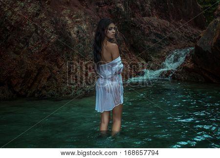 Romantic brunette beauty wearing white wet shirt standing in the water between rocks near beautiful small waterfall