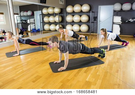Full length of male and female friends doing pushups on mat in gym