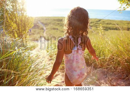 Young girl standing on a dune overlooking the view of the sea