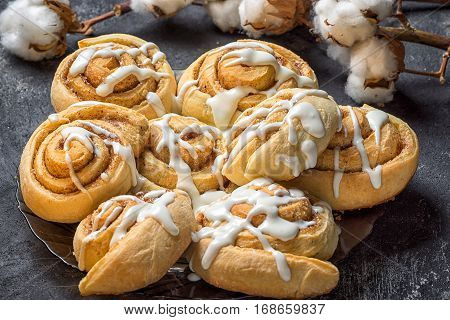 French sweet cinnamon rolls on a plate on a dark background with cotton bolls in the background